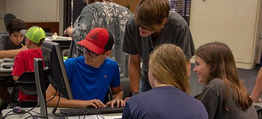 Teens at library gathered around computer
