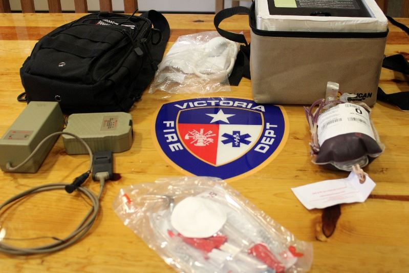 Equipment including an ice chest, a bag of frozen blood and medical tubes laid out on a table.