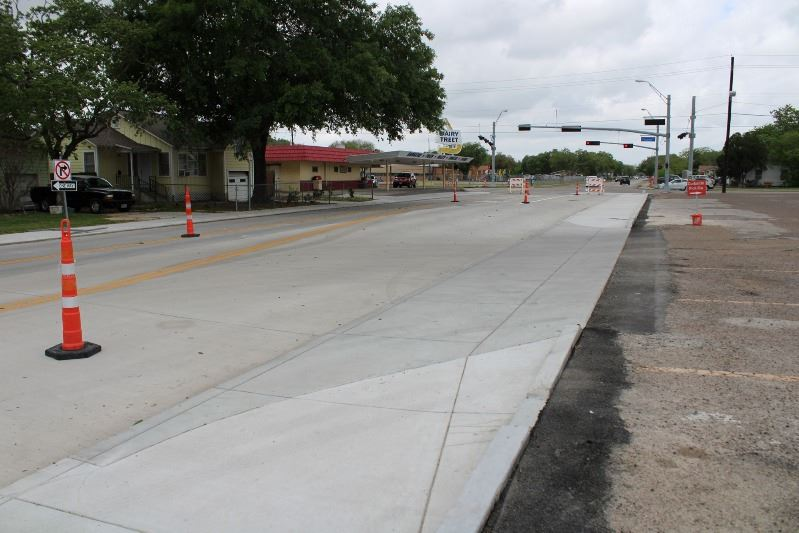 A concrete road bordered by a new sidewalk. The road is marked with cones and barricades.