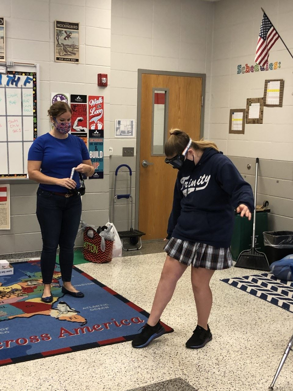 A woman watches a uniformed girl wearing impairment goggles try to walk in a line in a classroom.