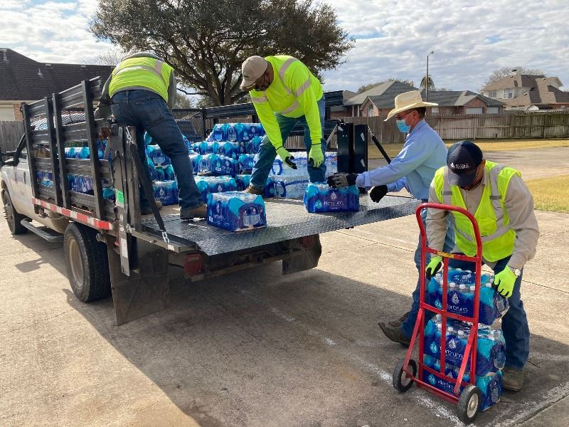 Workers unload cases of bottled water from a truck and place them on a dolly.