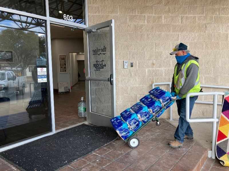 Man pushes dolly of bottled water through open glass door marked The Vine School.
